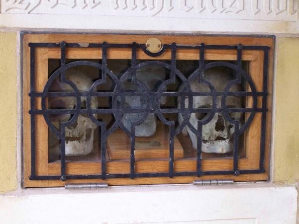 skull;s behind metal railings in a church lychgate