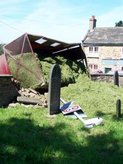 a farm truck fallen over onto a churchyard wall