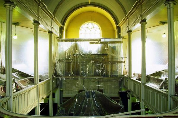 a congregational church swathed in protective plastic sheeting