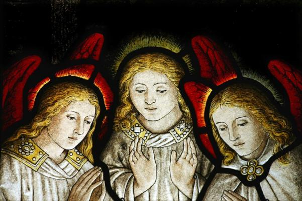 stained glass window of three angels looking down