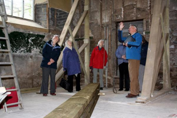 a group being shwon around building work taking place in a meeting house
