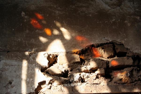 badly worn stone wall with stained glass reflected onto it