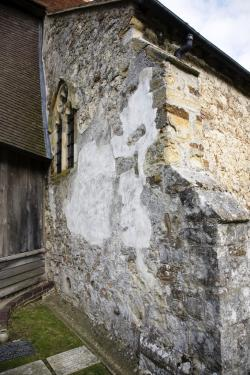 a church wall patched with cement render and mortar