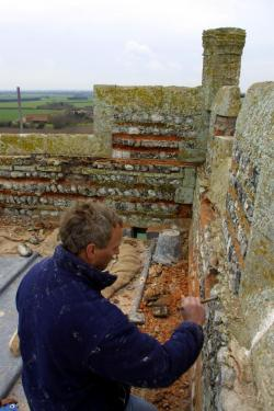 a workman repairing the pebble wall of a church