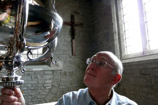 a man examining a lamp in a church