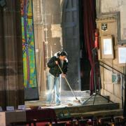 a woman sweeping a church floor