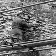 a man checkingthe condition of a stone wall